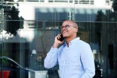 Усмехаясь бизнесмен говоря на мобильном телефоне Стоковые Изображения