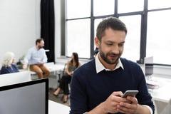 Усмехаясь бизнесмен говоря на мобильном телефоне Стоковые Изображения RF