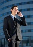 Усмехаясь бизнесмен говоря на мобильном телефоне outdoors Стоковая Фотография
