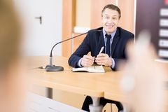 Усмехаясь бизнесмен говоря на пресс-конференции Стоковая Фотография