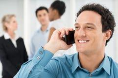 Усмехаясь бизнесмен говоря на сотовом телефоне Стоковые Фото