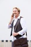 Усмехаясь бизнесмен говоря на сотовом телефоне Стоковое Фото
