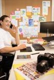 Усмехаясь бизнесмен говоря на телефоне на творческом офисе Стоковая Фотография