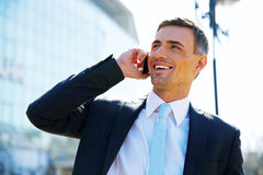 Усмехаясь бизнесмен говоря на телефоне Стоковые Фото