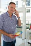 Усмехаясь бизнесмен говоря на умном телефоне в офисе Стоковые Изображения RF