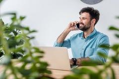 Усмехаясь бизнесмен говоря на smartphone пока использующ компьтер-книжку на рабочем месте Стоковая Фотография