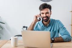 Усмехаясь бизнесмен говоря на smartphone пока смотрящ компьтер-книжку на рабочем месте Стоковое фото RF