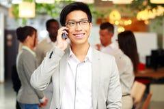 Усмехаясь бизнесмен говоря на smartphone Стоковые Изображения