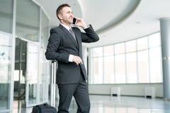 Усмехаясь бизнесмен говоря телефоном в авиапорте Стоковые Изображения RF