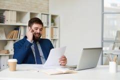 Усмехаясь бизнесмен говоря телефоном в офисе Стоковое Фото