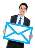 Усмехаясь бизнесмен держа знак конверта стоковые фото