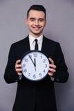 Усмехаясь бизнесмен держа настенные часы Стоковая Фотография RF