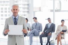 Усмехаясь бизнесмен держа пустой знак Стоковые Изображения
