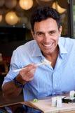 Усмехаясь бизнесмен есть суши с палочками Стоковые Фотографии RF