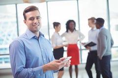 Усмехаясь бизнесмен используя мобильный телефон при коллеги обсуждая в предпосылке Стоковое Изображение RF