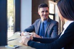 Усмехаясь бизнесмен и коммерсантка говоря в кафе Стоковые Фотографии RF