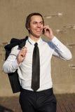 Усмехаясь бизнесмен идя и говоря на мобильном телефоне Стоковое фото RF
