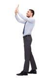 Усмехаясь бизнесмен нажимая вверх что-то мнимое Стоковая Фотография