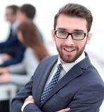 Усмехаясь бизнесмен на предпосылке офиса стоковая фотография rf