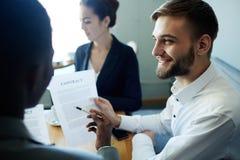 Усмехаясь бизнесмен объясняя контракт Стоковое фото RF