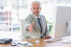 Усмехаясь бизнесмен достигая вне руку для рукопожатия Стоковое Изображение RF