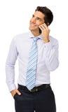 Усмехаясь бизнесмен отвечая умному телефону стоковые фотографии rf