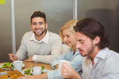 Усмехаясь бизнесмен при коллеги имея закуски Стоковое фото RF