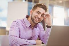 Усмехаясь бизнесмен работая с компьтер-книжкой Стоковые Изображения RF