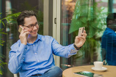 Усмехаясь бизнесмен разговаривая с умным телефоном и давать карточку к кельнеру в кафе стоковая фотография