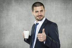 Усмехаясь бизнесмен рекомендует этот кофе стоковые изображения rf