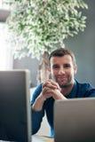 Усмехаясь бизнесмен сидя на компьютере в офисе Стоковые Изображения RF