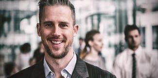 Усмехаясь бизнесмен стоя в офисе Стоковая Фотография