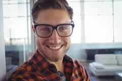 Усмехаясь бизнесмен стоя в офисе Стоковая Фотография RF