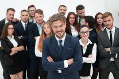 Усмехаясь бизнесмен стоя на предпосылке ее команды дела Стоковое Фото