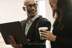 Усмехаясь бизнесмен с женским коллегой в офисе Стоковое Фото
