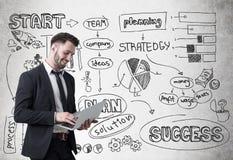Усмехаясь бизнесмен с компьтер-книжкой и startup эскизом Стоковое Фото