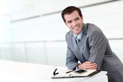 Усмехаясь бизнесмен с повесткой дня и smartphone Стоковые Изображения RF