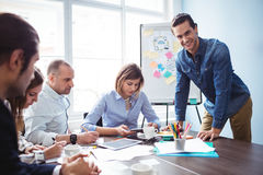Усмехаясь бизнесмен с сотрудниками в конференц-зале Стоковое Изображение RF