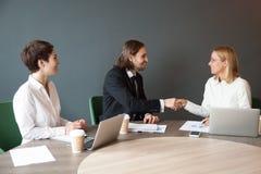 Усмехаясь бизнесмен тряся руку женского партнера на встрече группы Стоковое фото RF