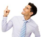 Усмехаясь бизнесмен указывая вверх стоковое изображение