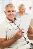 Усмехаясь бизнесмен читая документ Стоковая Фотография RF