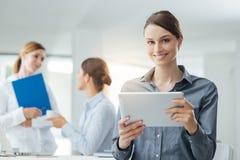Усмехаясь бизнес-леди используя таблетку Стоковое фото RF