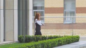 Усмехаясь бизнес-леди на телефоне на современном здании, замедленном движении акции видеоматериалы