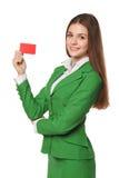 Усмехаясь бизнес-леди показывая кредитную карточку кредита без обеспечения в зеленом костюме, изолированном над белой предпосылко Стоковые Фотографии RF