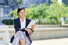 Усмехаясь бизнес-леди работая на таблетке Стоковое Фото