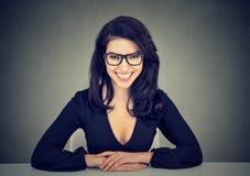 Усмехаясь бизнес-леди сидя на таблице смотря камеру стоковая фотография