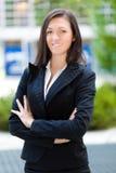 Усмехаясь бизнес-леди стоя внешний стоковая фотография