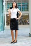 Усмехаясь бизнес-леди стоя внешний стоковое фото
