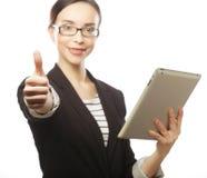 Усмехаясь бизнес-леди с выставкой большого пальца руки таблетки поднимающей вверх. Стоковая Фотография