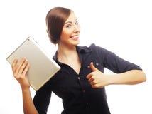Усмехаясь бизнес-леди с выставкой большого пальца руки таблетки поднимающей вверх. Стоковые Фото